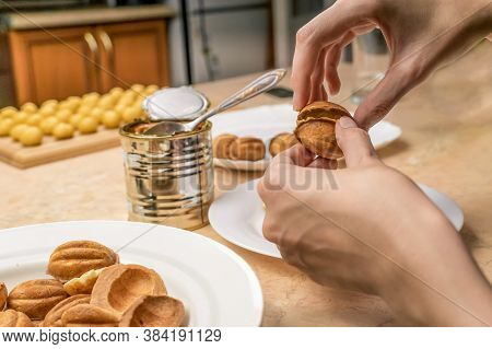 Women's Hands Connect The Halves Of The Cookie Nut Filled With Boiled Condensed Milk Over The Table