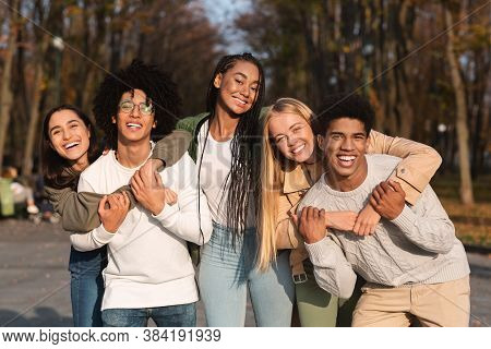 Positive Group Of Multiracial Young Friends Having Fun At Public Park, Hugging And Smiling