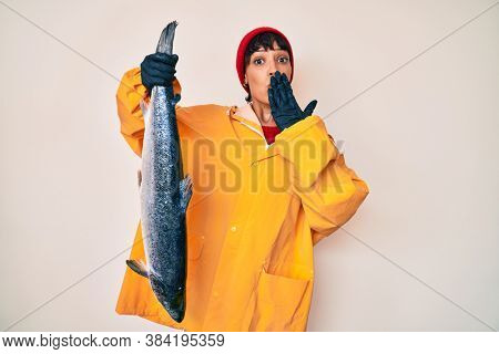Beautiful brunettte fisher woman wearing raincoat holding fresh salmon covering mouth with hand, shocked and afraid for mistake. surprised expression