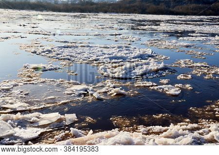 Ice Drift On A River With Blue High Water And Big Water, White Snow Broken Ice Full Of Hummocks In I