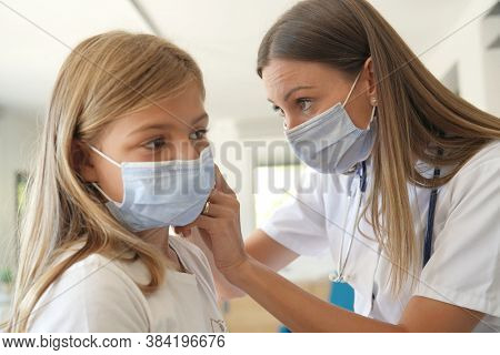 Kid at doctor's office with protection face mask having temperature checked