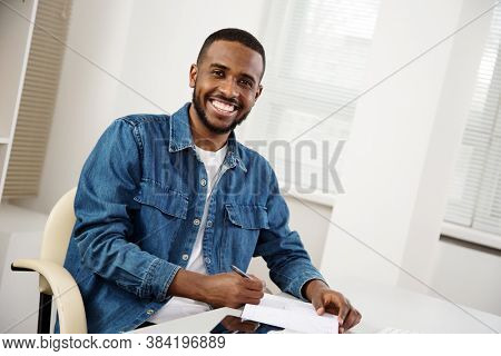 Happy handsome african american creative businessman smiling while looking at camera in office