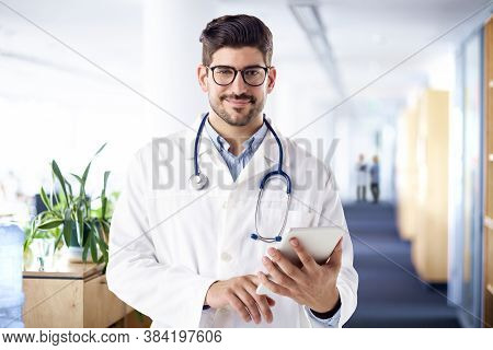 Shot Of Male Doctor Using Digital Tablet While Standing On The Hospital's Foyer.