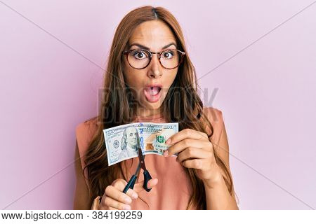 Young brunette woman cutting dollars with scissors for currency devaluation afraid and shocked with surprise and amazed expression, fear and excited face.