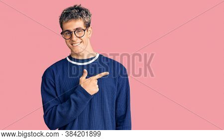 Young handsome man wearing casual clothes and glasses cheerful with a smile of face pointing with hand and finger up to the side with happy and natural expression on face