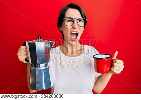 Young brunette woman with short hair drinking italian coffee angry and mad screaming frustrated and furious, shouting with anger looking up.
