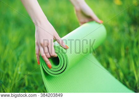 Close Up Hands Unrolling Bright Green Exercise Mat.