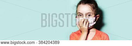 Panoramic Portrait Of Child Girl Wearing Medical Face Mask On The Background Of Cyan Color.
