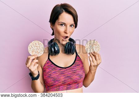 Young brunette woman with short hair wearing sportswear holding rice cakes in shock face, looking skeptical and sarcastic, surprised with open mouth