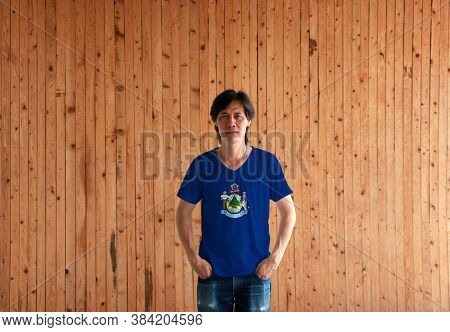 Man Wearing Maine Flag Color Shirt And Standing With Two Hands In Pant Pockets On The Wooden Wall Ba