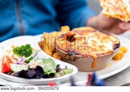Food On The English Pub Such As Portion Of Lasagne, Chips And Salad
