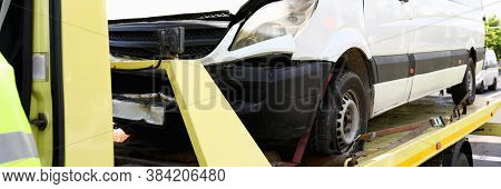 Wrecked Car Stands On Tow Truck Closeup. Car Evacuation Services Concept