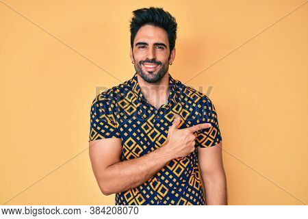 Handsome hispanic man with beard wearing 80s disco style shirt cheerful with a smile of face pointing with hand and finger up to the side with happy and natural expression on face
