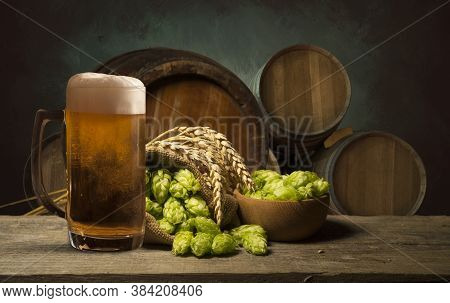 Beer. Still Life With Vintage Beer Barrel And Glass Light Beer. Fresh Amber Beer Concept. Green Hop