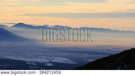 misty evening landscape with fog in winter valley