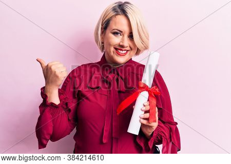 Beautiful blonde plus size woman holding graduated degree diploma over pink background pointing thumb up to the side smiling happy with open mouth