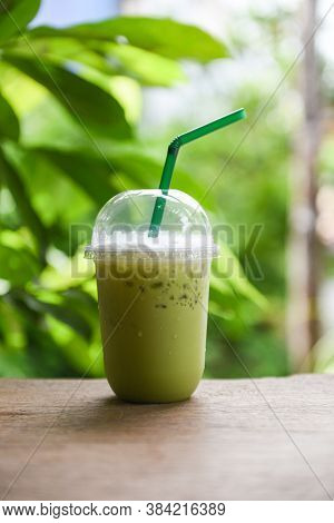 Iced Drinks Green Tea Smoothie / Matcha Green Tea With Milk On Plastic Glass On The Wooden Table And