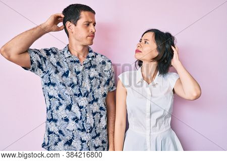 Beautiful couple wearing casual clothes confuse and wondering about question. uncertain with doubt, thinking with hand on head. pensive concept.