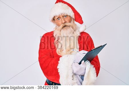Old senior man with grey hair and long beard wearing santa claus costume writting list in shock face, looking skeptical and sarcastic, surprised with open mouth