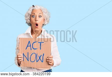 Senior grey-haired woman holding act now banner scared and amazed with open mouth for surprise, disbelief face