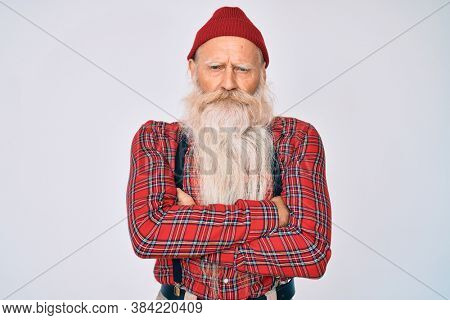 Old senior man with grey hair and long beard wearing hipster look with wool cap skeptic and nervous, disapproving expression on face with crossed arms. negative person.