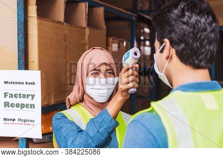 Muslim Woman Worker Wearing Surgical Mask And Hijab Uses Medical Digital Infrared Thermometer Measur