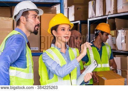 Asian Assistant Manager Woman Reporting To White Caucasian Manager Of Warehouse Worker With Muslim A