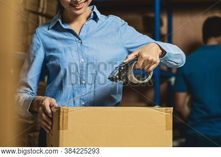 Closeup Of Warehouse Worker Woman Packing Cardboard Box With Sticky Tape With Indian Worker Man In L