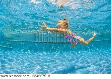 Funny Portrait Of Child Learning Swimming, Dive In Blue Pool With Fun - Jumping Deep Down Underwater