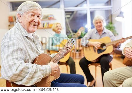 Cheerful senior man playing guitar in a guitar course at the community college