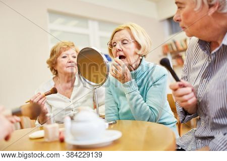 Elderly woman applies lipstick while styling in the make-up make-up course in the retirement home