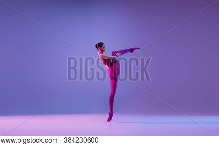 Tender. Young And Graceful Ballet Dancer Isolated On Purple Studio Background In Neon Light. Art, Mo