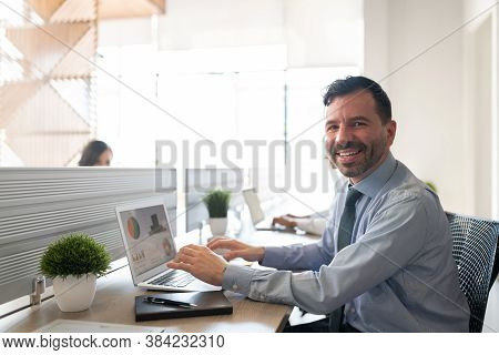 Portrait Of A Smiling Mid Adult Businessman Sitting At His Desk With Laptop In Office