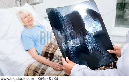Experienced Doctor Is Holding An X-ray Of The Cervical Spine Of Elderly Woman. Treatment Of Spine Di