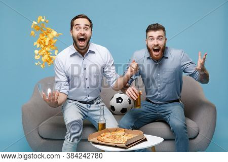 Excited Men Guys Friends Colleagues In Casual Shirt Sit On Couch Isolated On Blue Background. Sport