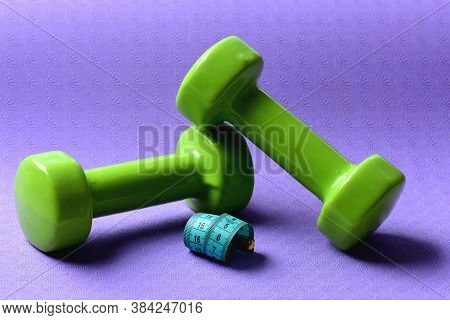 Barbells In Small Size Next To Cyan Ruler, Close Up.