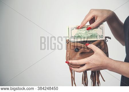 Young Woman Pulls Out Dollar Banknotes Money From Brown Wallet Bag
