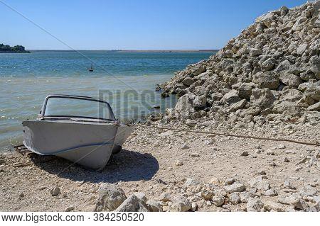 Empty old metal fishing motor boat docked near lake o r sea shore
