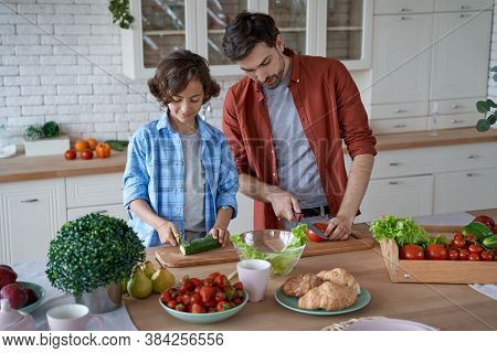 Preparing Lunch Together. Young Father Teaching His Son How To Cut Fresh Vegetables, Preparing Salad
