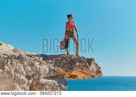 Woman In Beachwear With Suitcase And Glasses. Ocean View From Cliff. Time For Travel Or Summer Holid