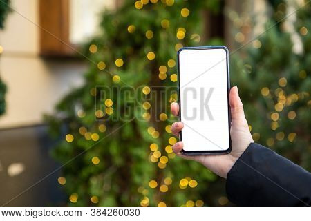 Woman Hand Holding Phone With White Screen Christmas Tree On Background