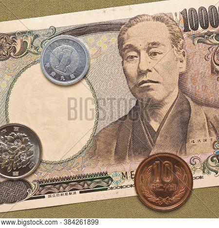 Japanese Money: Ten Thousand Yen Bill And Coins. Green Textile Background. Macro