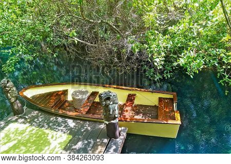 A Yellow Wooden Boat Is Moored. The Water In The River Is Turquoise. On The Shore There Are Tropical