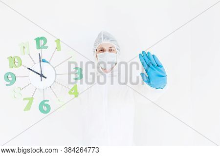 A Man In A Protective Suit, Gloves And Face Mask Is Holding A Watch And Making A Gesture Of Stop. Th