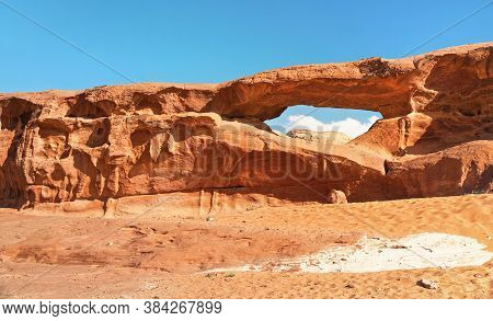 Little Arc Or Small Rock Window Formation In Wadi Rum Desert, Bright Sun Shines On Red Dust And Rock