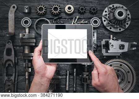 Car Service Worker Is Holding A Blank Screen Digital Tablet Above Spare Parts Background. Car Spare