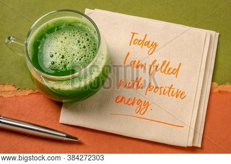 today I am filled with a positive energy - inspirational note on a napkin with a glass of fresh green cucmber juice, lifestyle and positivity concept