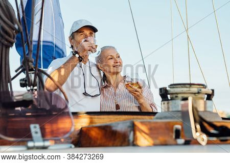 Portrait Of Senior Couple Standing On A Private Sailboat And Drinking Wine. Woman And Man With Bocal