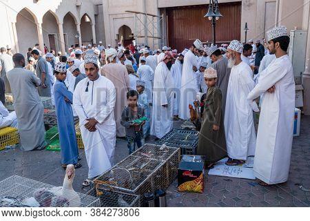 Nizwa, Oman, December 2, 2016: A local crowd at the bird market in Nizwa, Oman - a part of weekly Friday market