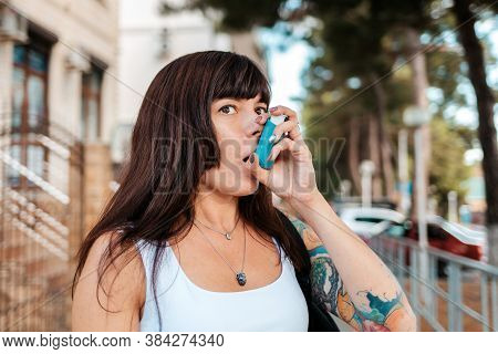A Woman With A Tattoo On Her Arm, Inhaling Medicine From An Inhaler. The Concept Of Asthma